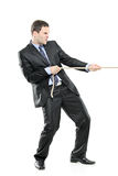 A young businessman pulling a rope. Isolated on white background stock images