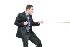 A young businessman pulling a rope Stock Photo