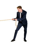 Young businessman pulling a rope. Isolated on white background Royalty Free Stock Photos