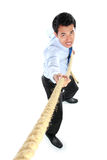 Young businessman pulling a rope while standing Royalty Free Stock Image