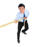 Young businessman pulling a rope while standing Stock Image