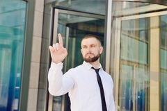 A young businessman pushes his index finger against a virtual sc. Reen on the background of an office building. Click on the screen. Virtual Display royalty free stock photography