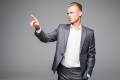 Handsome young businessman pushes invisible button on a gray background. A young businessman pushes invisible button on a gray background royalty free stock photos