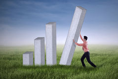 Young businessman pushing a bar chart outdoor Royalty Free Stock Image