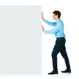 Young businessman pushing a blank billboard on white Stock Images