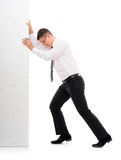 Young businessman pushing a blank board on white. Image is isolated on a white background Royalty Free Stock Photography