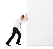 Young businessman pushing a giant white blank banner. Business man pushing a big blank banner over white background. Image taken in a studio Royalty Free Stock Image