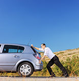 Young businessman pushing his car with empty fuel tank Royalty Free Stock Image