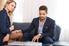 Young businessman put hands on businesswoman leg Stock Photos