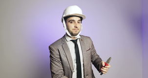 Young businessman puts on hard hat or helmet and smiling. stock video footage