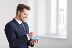 Young businessman putting coin into piggy bank indoors. Money savings concept royalty free stock photography