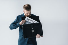 Young businessman putting newspaper in briefcase Royalty Free Stock Photography