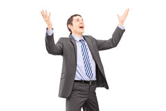 Young businessman with raised hands waiting something to fall Stock Photo