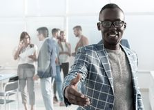 Young businessman reaching out for a handshake. Concept of partnership stock photography
