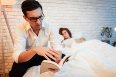 Young businessman read book near sleeping young woman. Man in glasses concentrated on reading book. Handsome men enthusiastically reading book. Beautiful women Stock Photos