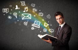 Young businessman reading a book with multimedia icons coming ou Stock Photos