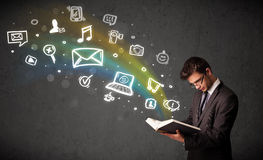 Young businessman reading a book with multimedia icons coming ou Royalty Free Stock Image