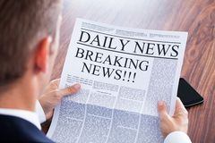 Young businessman reading breaking news. On Newspaper royalty free stock photography
