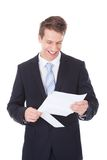 Young Businessman Reading Document Over White Background Royalty Free Stock Image