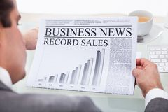Young businessman reading news on newspaper Stock Image