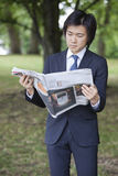 Young businessman reading newspaper at park Royalty Free Stock Photo
