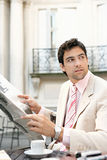 Attractive businessman reading paper in cafe. Stock Photos