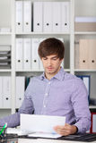 Young Businessman Reading Paper At Desk Stock Images