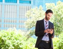 Young businessman reading text message on mobile phone Stock Photo