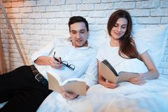 Young businessman reads book in bed with his wife. Couple are lying in bed at home. Royalty Free Stock Photos