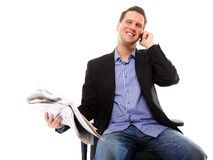 Young businessman reads newspaper while phoning Royalty Free Stock Photos