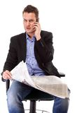 Young businessman reads newspaper while phoning Royalty Free Stock Image
