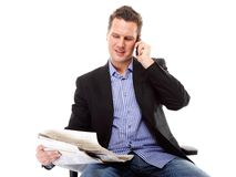 Young businessman reads newspaper while phoning Stock Image