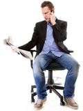 Young businessman reads newspaper while phoning Royalty Free Stock Photo