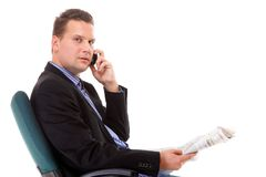 Young businessman reads newspaper while phoning Stock Photo