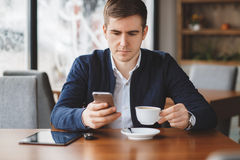 Young businessman reads SMS on phone in cafe. A handsome young man,dark hair with brown eyes,dressed in a white shirt and a dark blue jacket,drinking coffee from Stock Photography