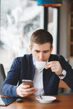 Young businessman reads SMS on phone in cafe Stock Photo