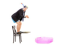 Young businessman ready to jump into a baby pool Royalty Free Stock Photos