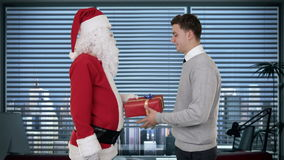 Young Businessman receiving a present from Santa Claus in a modern office, shaking hands, stock footage Royalty Free Stock Photo
