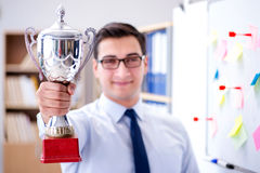 The young businessman receiving prize cup in office. Young businessman receiving prize cup in office stock images