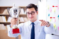 The young businessman receiving prize cup in office. Young businessman receiving prize cup in office royalty free stock photography