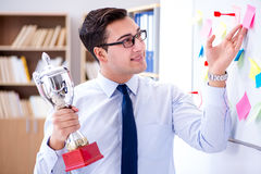 The young businessman receiving prize cup in office. Young businessman receiving prize cup in office stock image