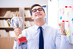 The young businessman receiving prize cup in office. Young businessman receiving prize cup in office royalty free stock images