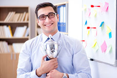 The young businessman receiving prize cup in office. Young businessman receiving prize cup in office stock photo