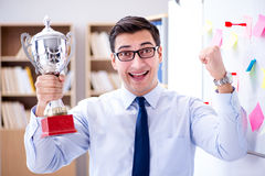 The young businessman receiving prize cup in office Stock Photos