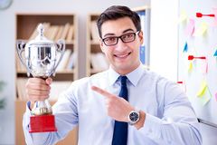 The young businessman receiving prize cup in office. Young businessman receiving prize cup in office stock photography