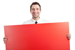 Young Businessman with red blank sign smiling. Young Businessman holding red blank sign and smiling isolated on white Royalty Free Stock Image