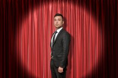 Young businessman on red stage curtains background stock image