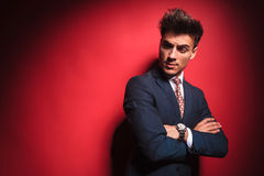 Young businessman with red tie frowning with hands crossed. Portrait of confident young businessman in black suit with red tie posing with hands crossed while Royalty Free Stock Image