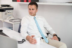 Young Businessman Relaxes Sitting In The Office Stock Images
