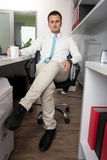 Young Businessman Relaxes Sitting In The Office Royalty Free Stock Photos